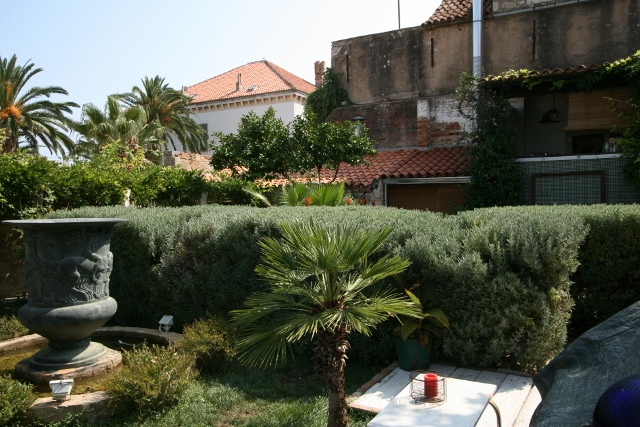 Courtyard garden of Lola's. Tables seperated by hedges and fountains.
